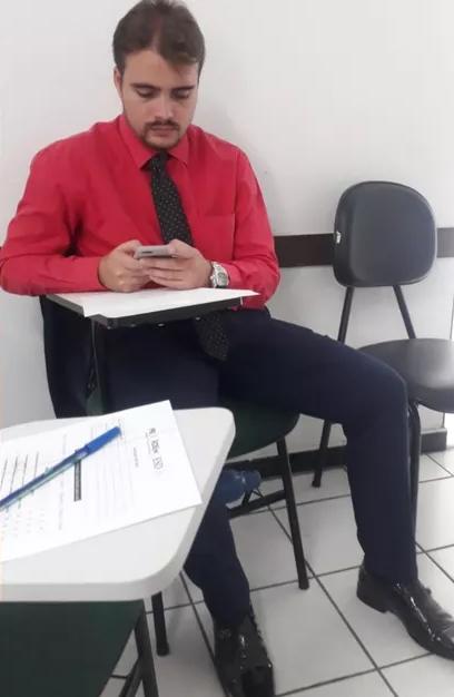 Foto de João Cláudio gravando as aulas no celular para estudar por meio dos áudios.